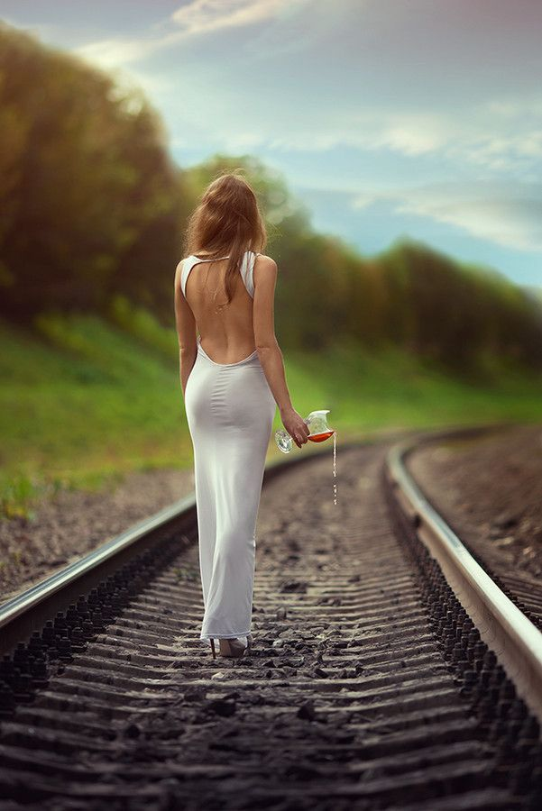 Woman walking on train tracks and  wasting wine