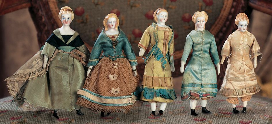 "Five German Bisque Miniature Dolls with Different Sculpted Hair Styles. each about 4 1/2"" (11 cm.) Each has bisque shoulder head with blonde sculpted hair in ornate style,painted facial features,muslin body,bisque lower arms and legs,each wearing original costume."