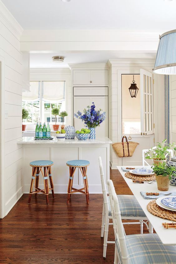 In this narrow, L-shaped kitchen, Bartholomew chose a traditional all-white foundation (shiplap walls, marble counters, Shaker cabinets, a Dutch door) and accessorized with pieces she has long admired, like French bistro stools, myrtle topiaries, Chippendale dining chairs, and a painting by Kayce Hughes.