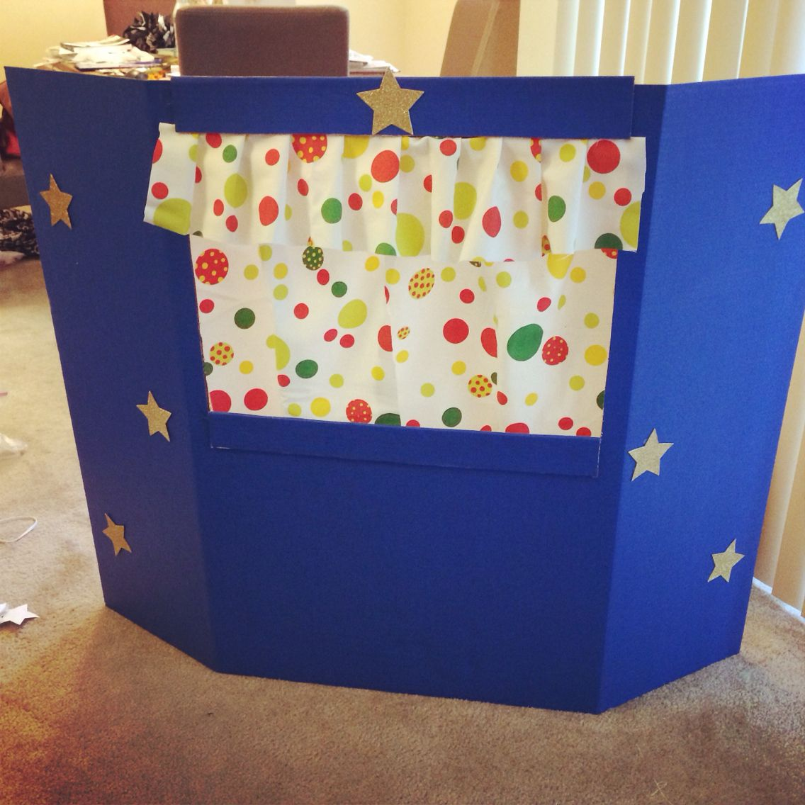 puppet theater made from a trifold poster board. i stapled curtains