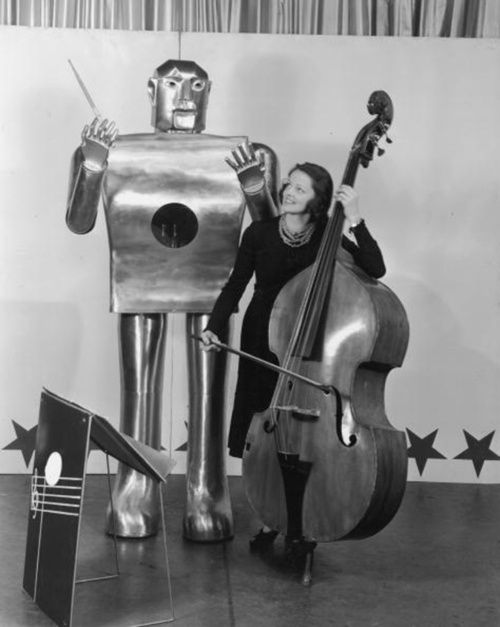 1939 :  Musician Lois Kendall plays the cello while a mechanical man named Elektro 'conducts' on stage as part of a Westinghouse Electric and Manufacturing Co demonstration at the World's Fair, Flushing Meadow Park, Queens, New York City.