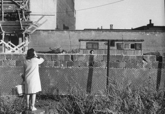 Not originally published in LIFE. A woman, foreground, who had escaped to West Berlin, speaks to her mother — who is still in East Berlin — in August 1961. (Stan Wayman—Time & Life Pictures/Getty Images)