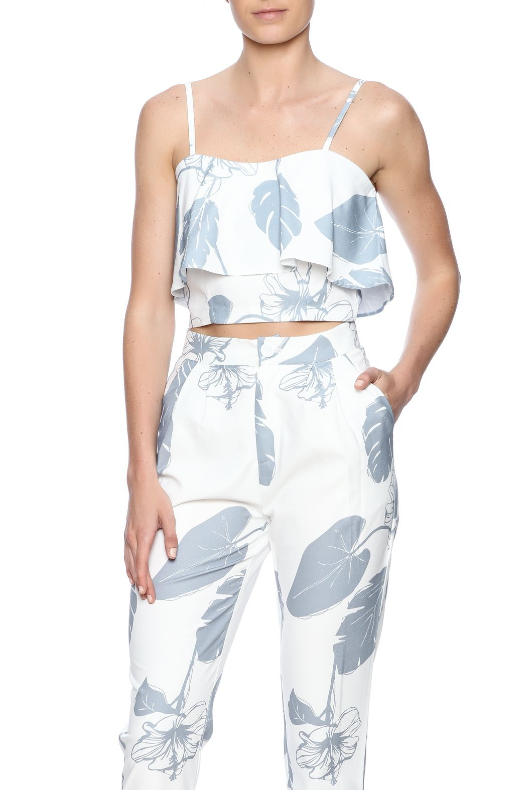 c746a8b7371 Spaghetti strap crop top with ruffle overlay in white base and silver floral  print. Adjustable straps and hidden zipper closure.