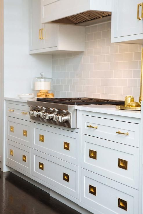 White shaker drawers accented with vintage brass inset ...