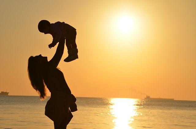 Foto de mamá alzando a su hijo hacia el cielo
