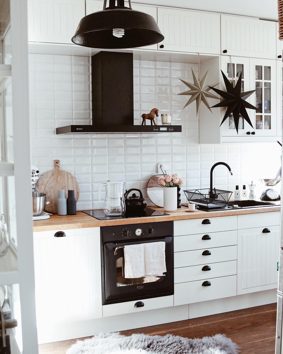Modern minimal white kitchen with black appliances, black