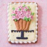 Galleta decorada con glasé. Un cake stand con una maceta de flores comestibles!