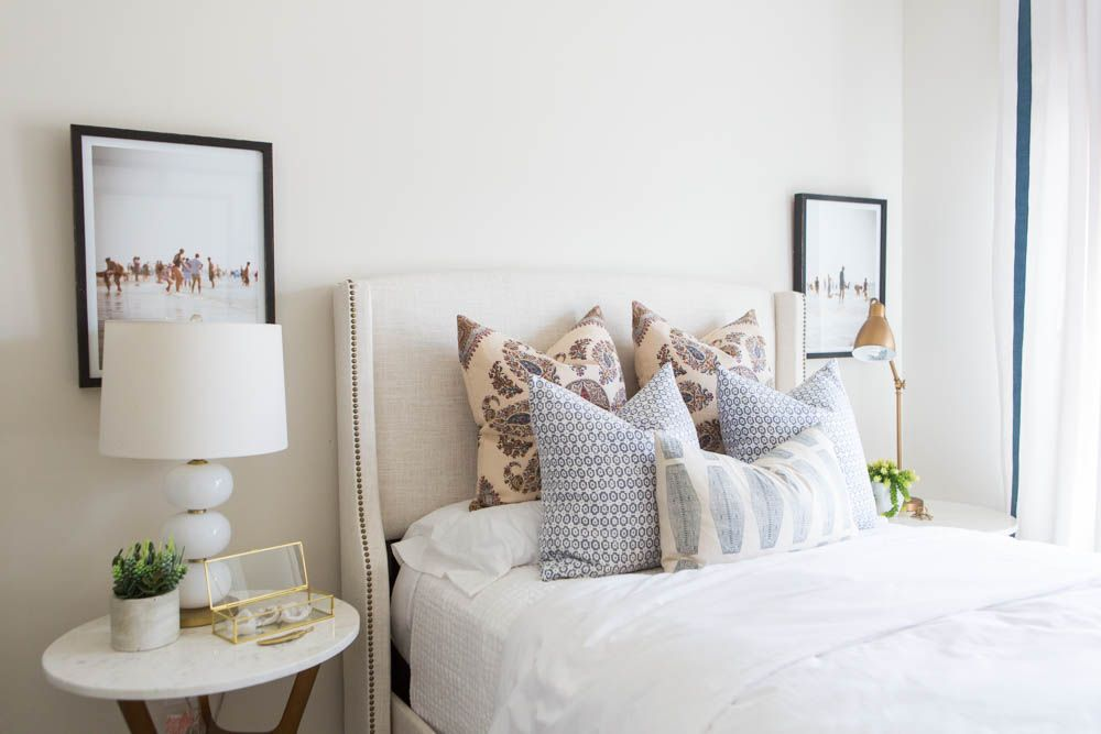 Lovely neutral bedroom with throw cushions, black personal frames. [Alden Model Master & Guest Bedrooms - House of Jade Interiors Blog]