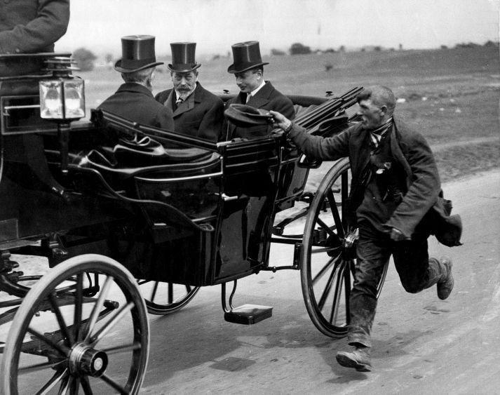 A beggar running alongside King George V's coach, 1920