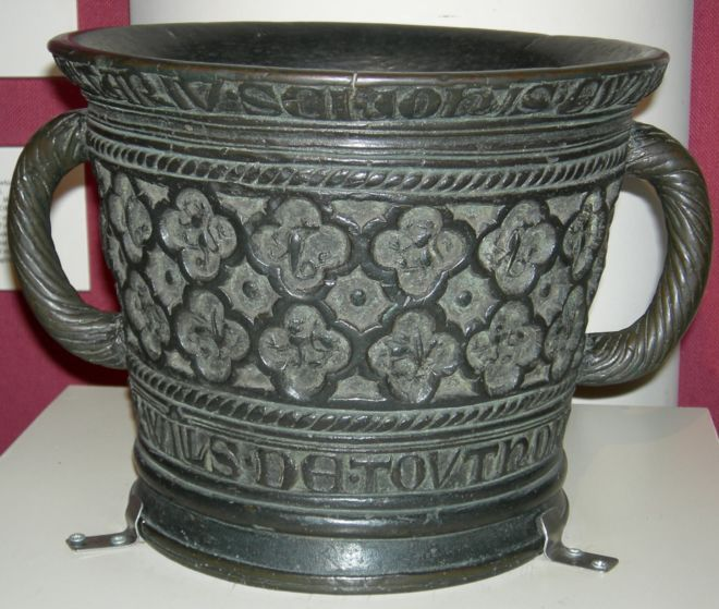 A mortar made from bell bronze with twisted detail on the handle and decorated with flowers and writing. ©York Museums Trust (Yorkshire Museum)