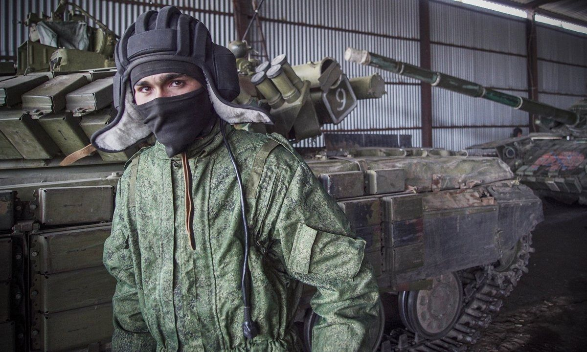 A Russiabacked separatist walks past tanks near