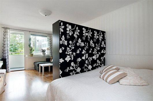 Una camera da letto con la parete dietro la testata rossa ...
