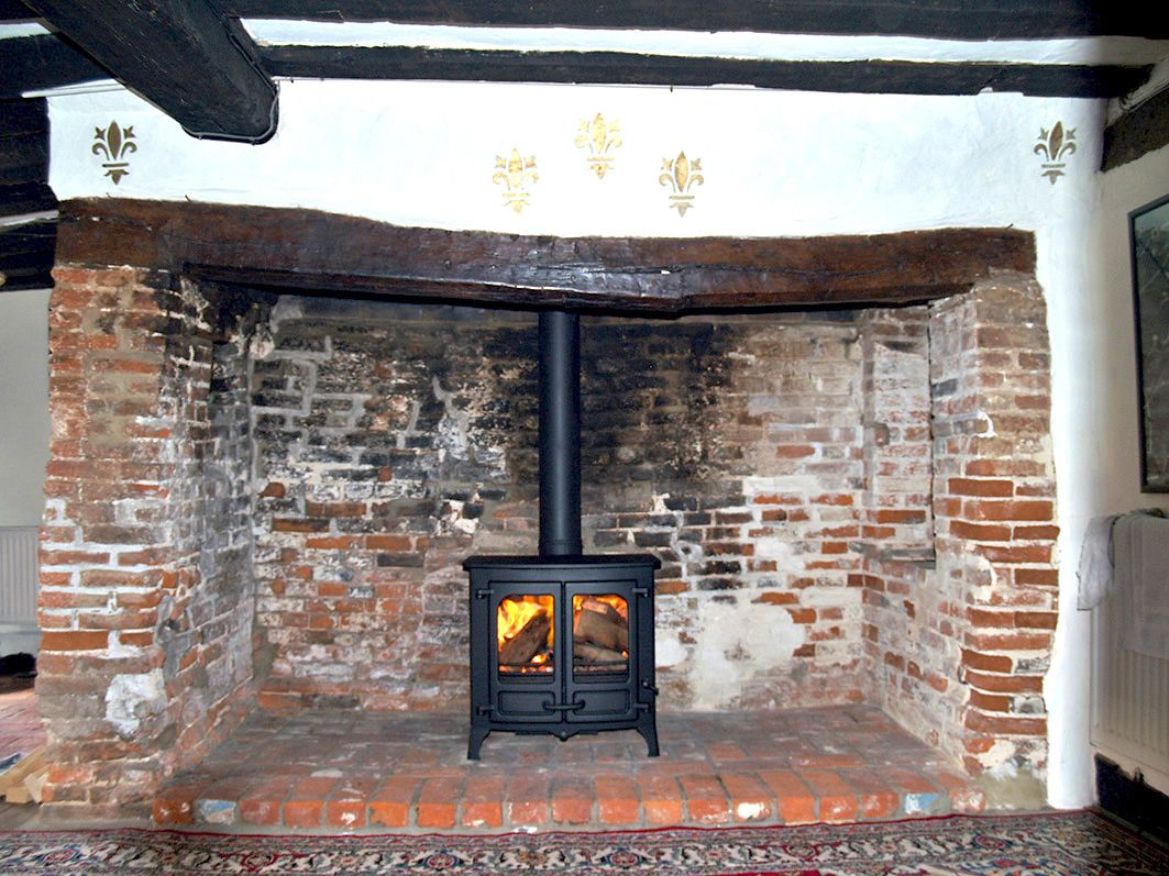 Charnwood island 2 wood burning stove installed in one of the oldest recorded red brick inglenooks