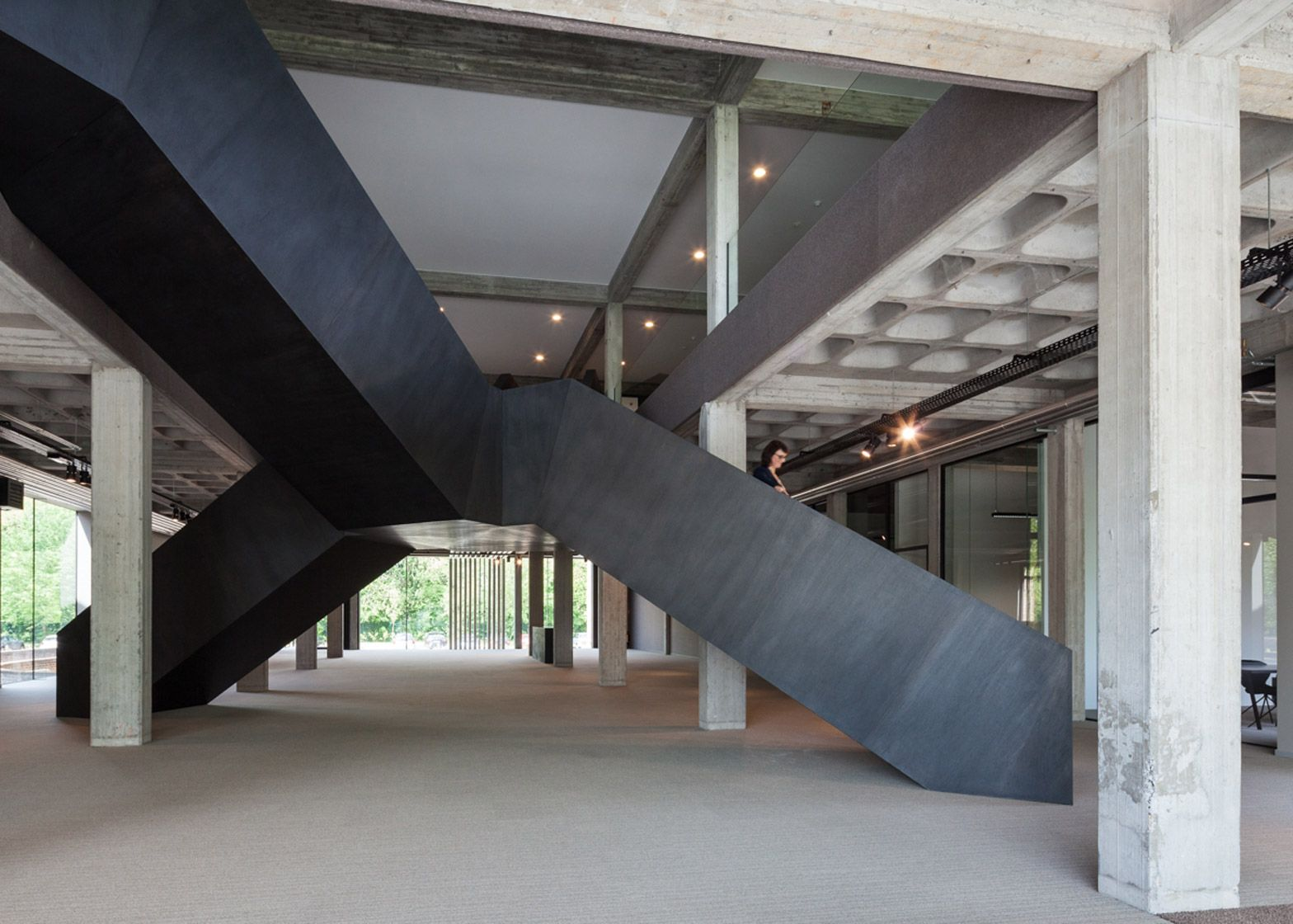 A multi-directional black staircase bridges the main entrance space in this converted office building in Belgium.
