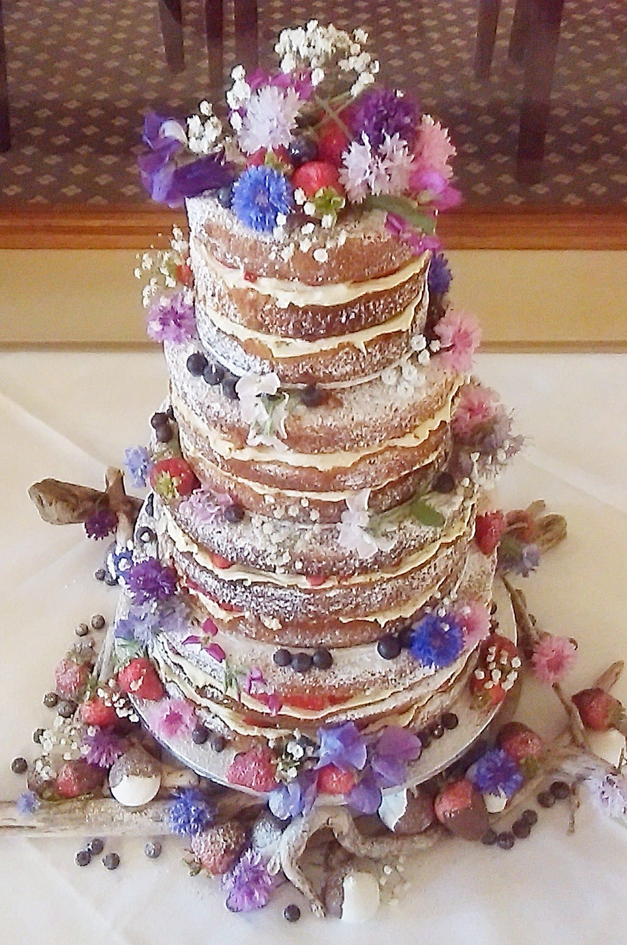 tier naked wedding cake decorated with home grown flowers fresh