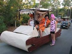 golf cart decorated for halloween as flinstone vehicle with the characters too fun idea