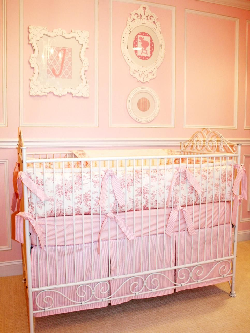 A white metal crib with pink and white toile bed linens add the ...