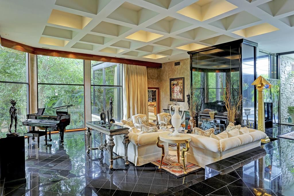 Sunken living room, wall of windows, gleaming black granite walls.