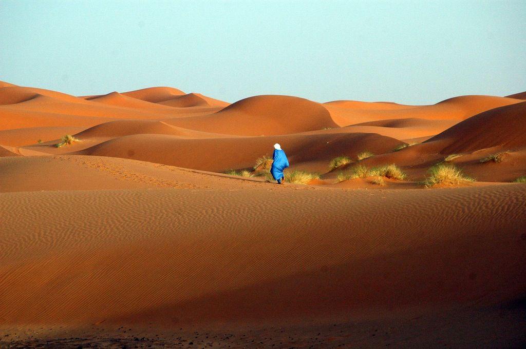 Tuareg walking across the desert in Erg Chebbi, Morocco. Photo by Maureen in 2007 (Flickr)