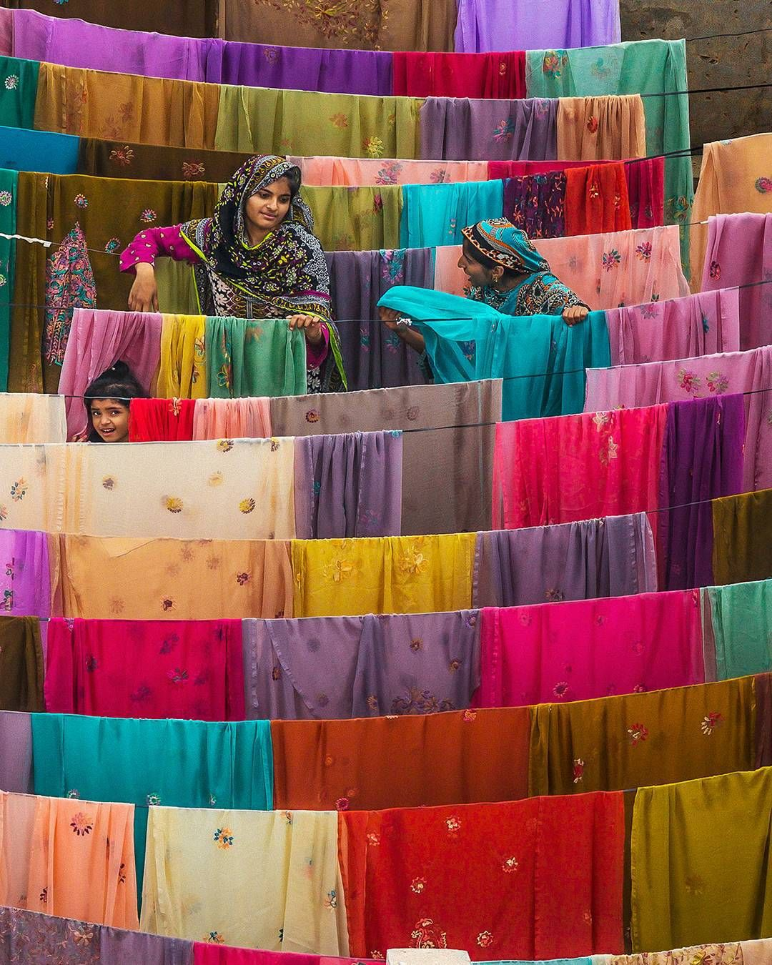Textiles Drying In Bahawalpur, Punjab, Pakistan. The Punjab region is the economic heart of Pakistan. The textile industry accounts for more than half of exports and 20 percent of the workforce. This sector, however, faces challenges: an unstable rupee, competition from neighboring countries, and power supply shortages that prevent factories from producing at full capacity.  Image and caption from 'Human: A Portrait of Our World' by Yann Arthus-Bertrand. #WhatMakesUsHuman