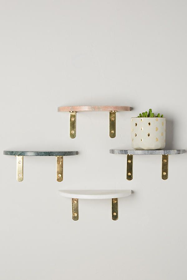 Use brass brackets and a stone tile to create a small shelf.