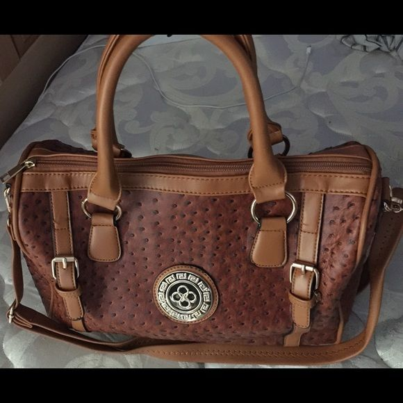 "Brown Barrel Satchel FauxLeatherZipper Crossbody Price Firm Brand New With Tags Gorgeous Satchel in a Brown Neutral Color with Gold Accents. Beautiful Design, faux leather, double top handles, one adjustable/removable Crossbody Strap, Gold Hardware. One zipper pocket outside, one zipper pockets and two zipper pockets inside...You Will Love it!!! Buckles Barrel Satchel Brown. 11""x14""x7"" Bags Satchels"