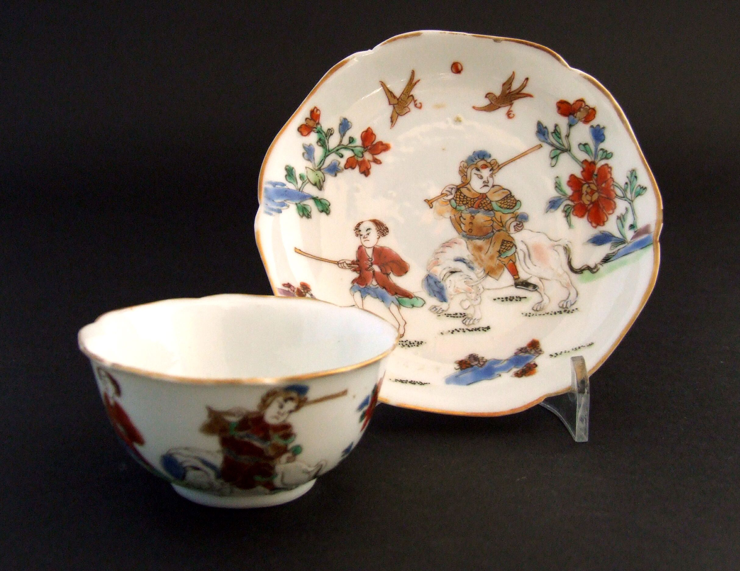 A Rare Chinese Export Porcelain Famille Rose Teabowl and Saucer, Yongzheng Period 1723-1735. This rare, well painted Famille Rose Porcelain teabowl and saucer is painted with a curious scene of a armoured Chinese solider riding a white elephant with an attendant in European dress.
