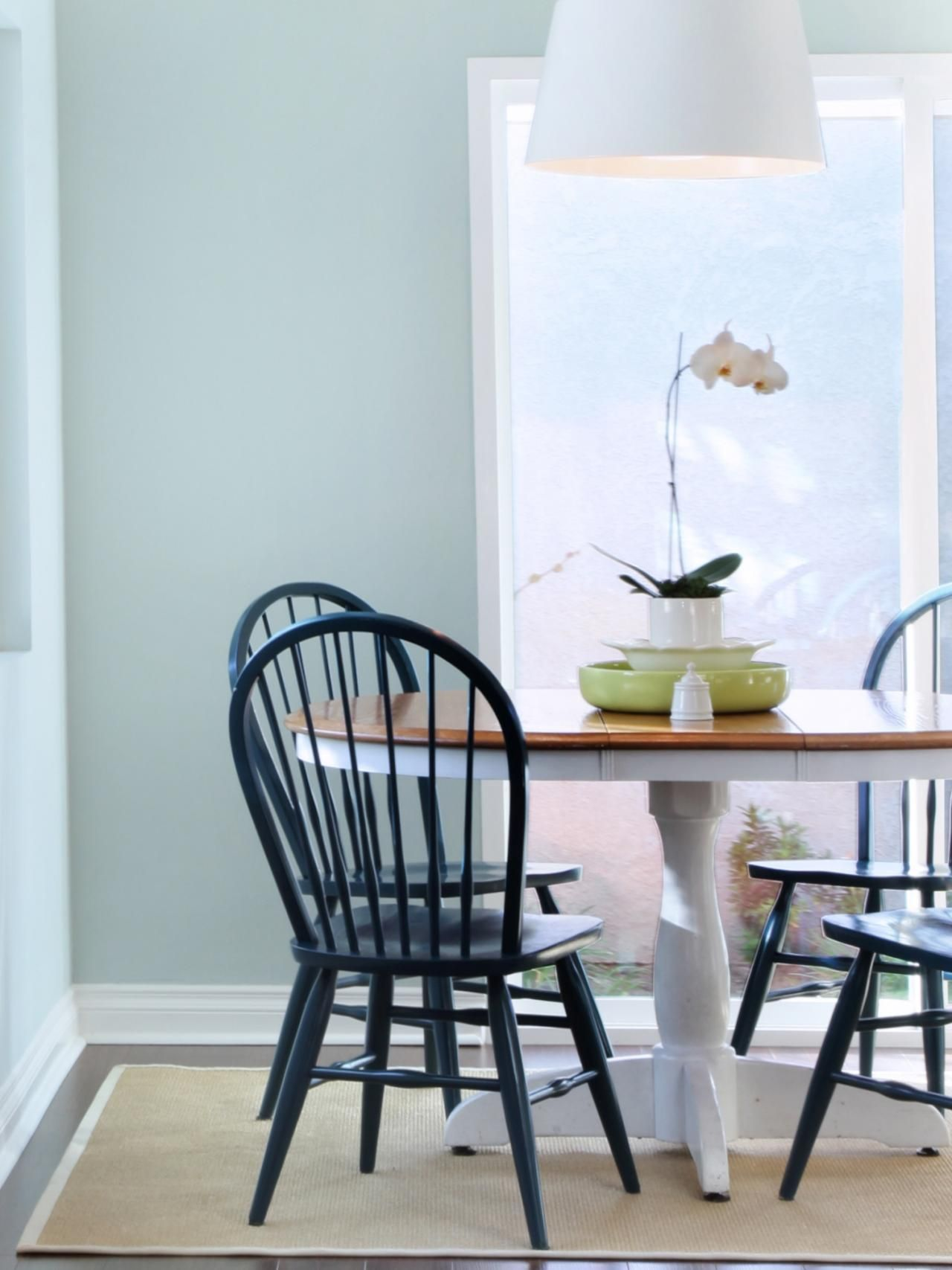 This cottage-inspired dining room is kept causal thanks to a painted wood table and black Windsor chairs. A large white pendant is a modern counterpoint to the traditional chairs and sturdy table.