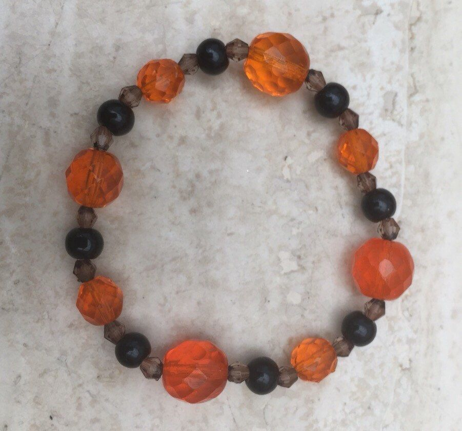 A personal favourite from my Etsy shop https://www.etsy.com/uk/listing/286547351/orange-faceted-and-black-beaded-bracelet