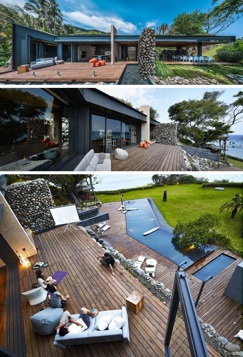 This modern house has an outdoor deck with a a water feature that turns into a waterfall on the lower level, home to an infinity swimming pool.