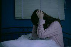 を持っている女性頭部ベッドに夜に stock photo