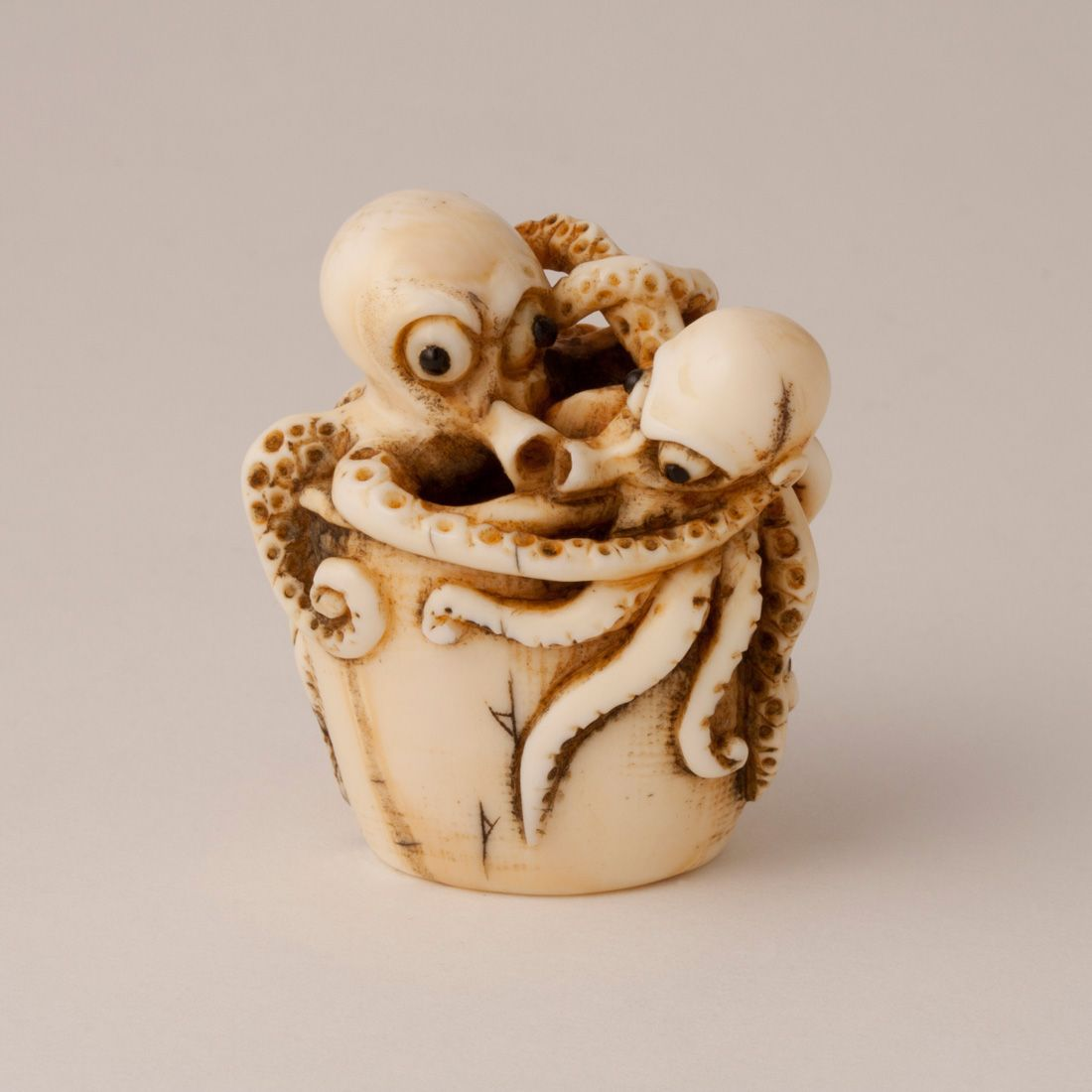 ivory netsuke of two octopi in a barnacle encrusted bucket, 19th century, by Ittokusai  根付
