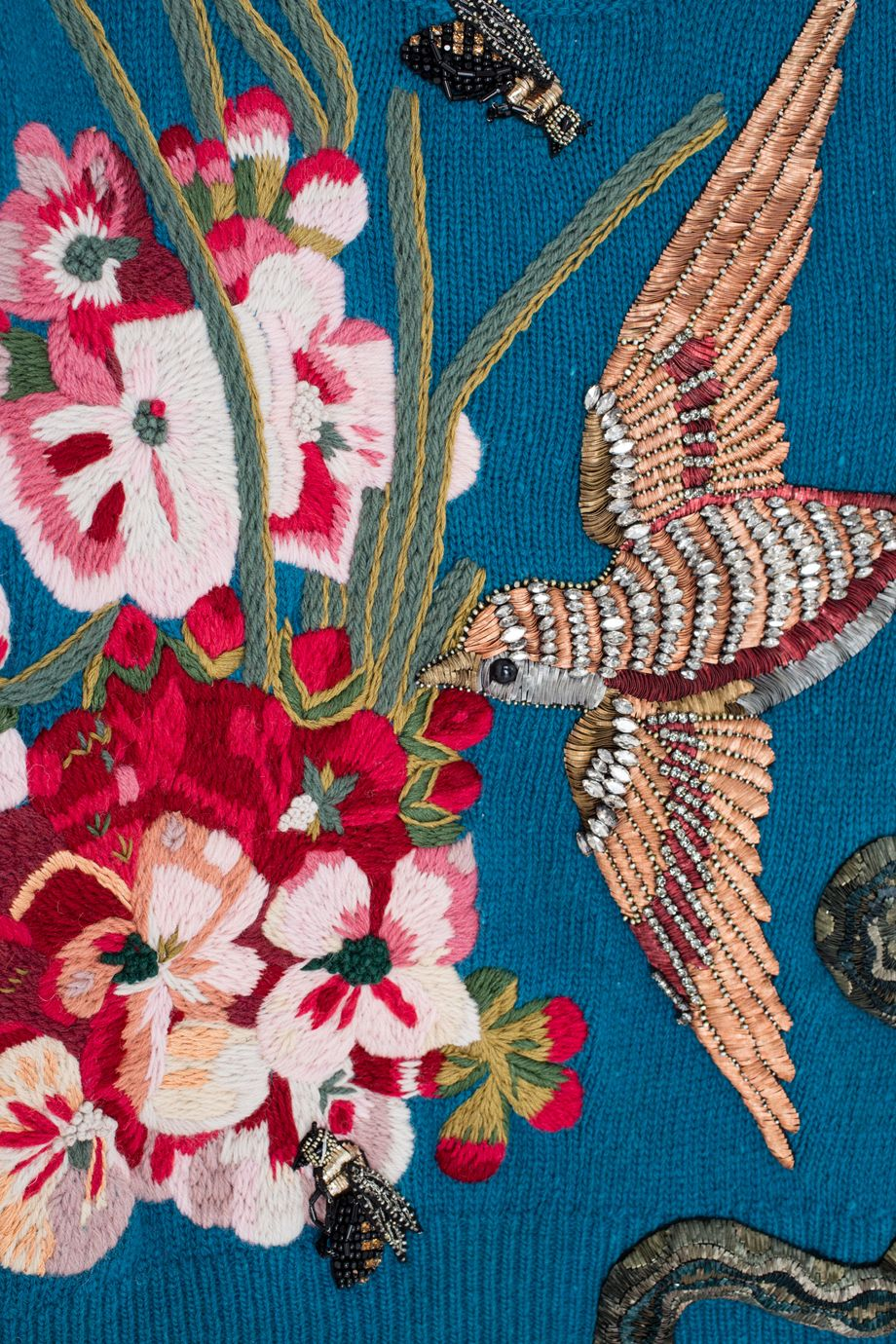 Вязаный свитер из шерсти мериноса бирюзового цвета. Модель декорирована жаккардовой вышивкой и стразами: яркие цветочные бутоны, птица, змея – главные «герои» этого мастхэва. Носите с прозрачными юбками (как это было на показе) или джинсами-клеш.