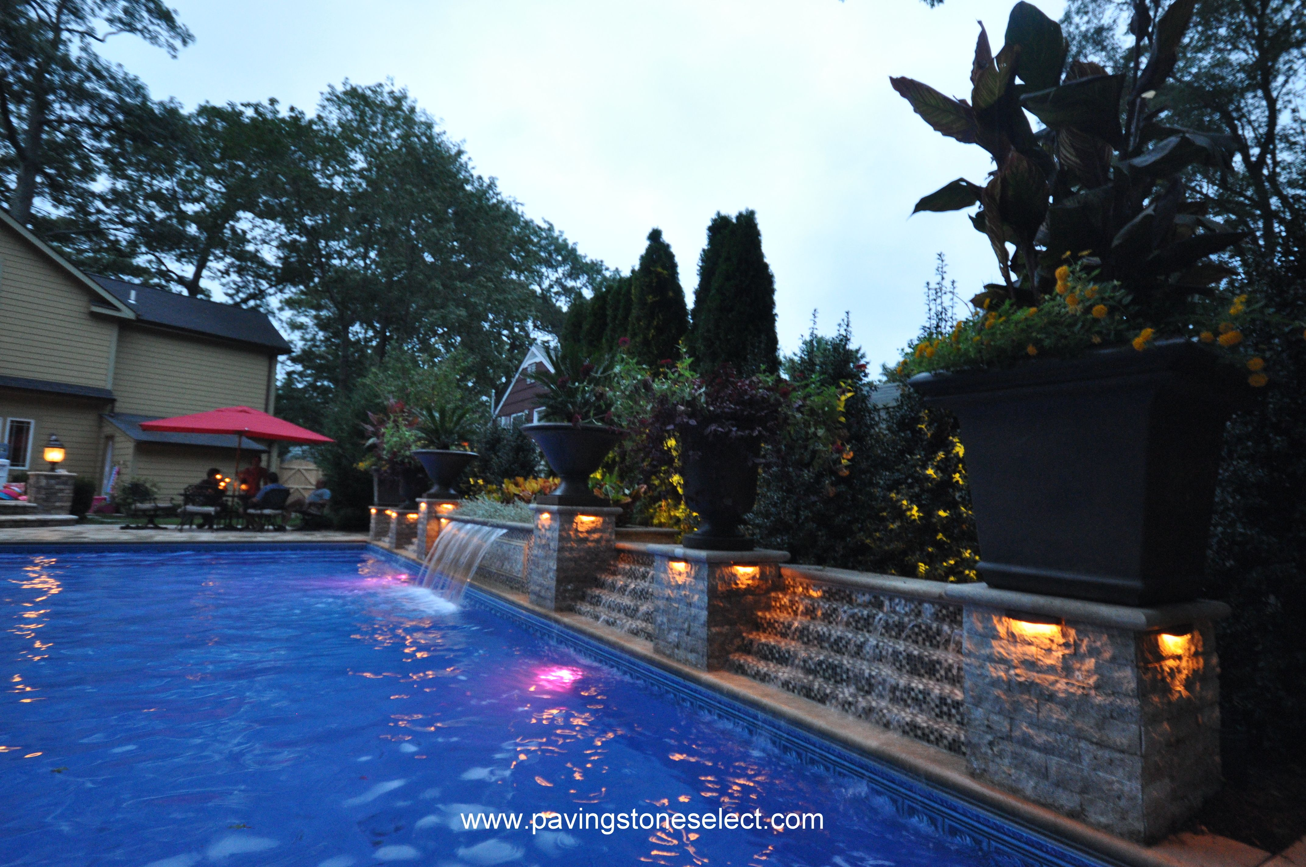 In this patio we see a beautiful backyard scene with ...