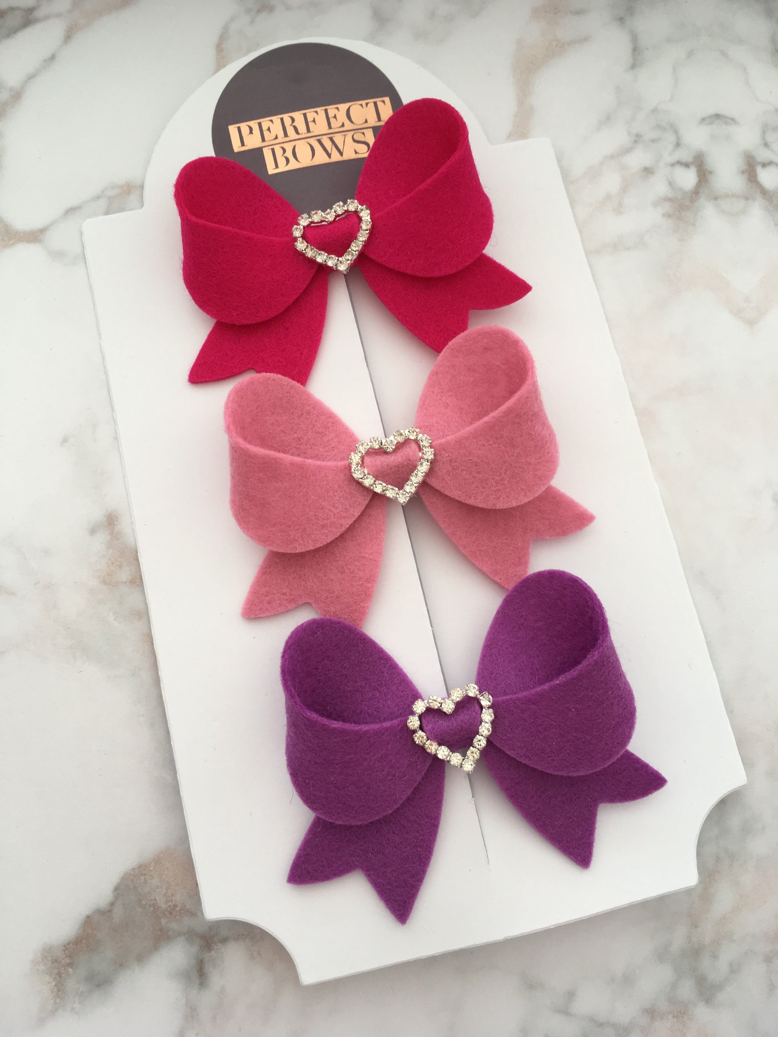 Heart Fancy BowAvailable on 3 coloursAvailable on a clip or a stretchy nylon headband which is one size, if you would