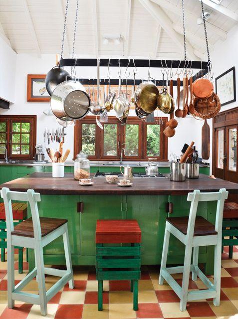 cocina rstica en verde y colores tierra con gran isla de madera central y utensilios colgados