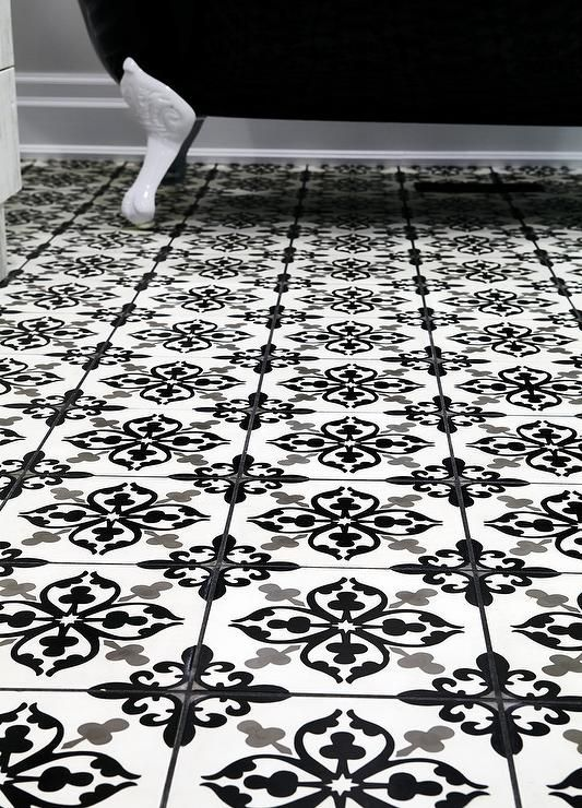 A Black And White Freestanding Clawfoot Tub Sits On Stunning Mosaic Fleur De Lis Floor Tiles