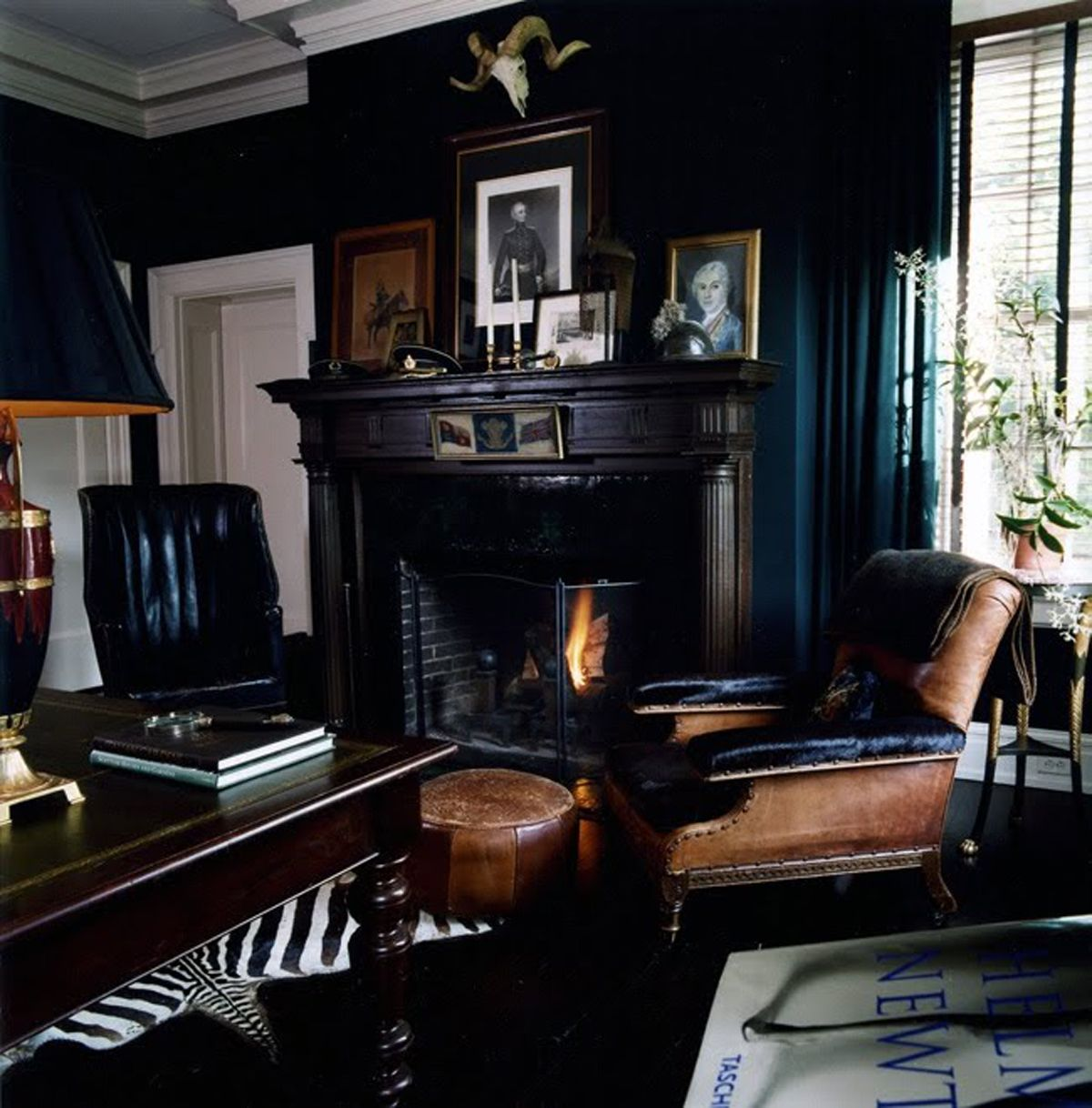 Gorgeous eclectic navy blue living room with classic black leather wingback chair and zebra Black white blue living room