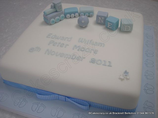 White square and blue themed christening cake with hand made sugar toys featuring a train, ball, and building blocks. Blue iced covered board with embossed feet, combined with blue gingham ribbon makes the final detail of this very popular cake design