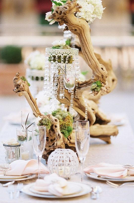 driftwood and small hanging chandelier for centerpieces. decorated with moss and fresh florals.