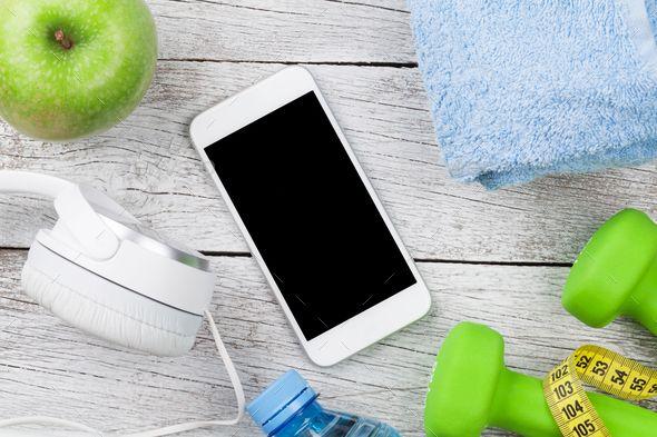 Fitness concept by karandaev. Fitness concept. Dumbbells, smartphone, headphones and apple on wooden...