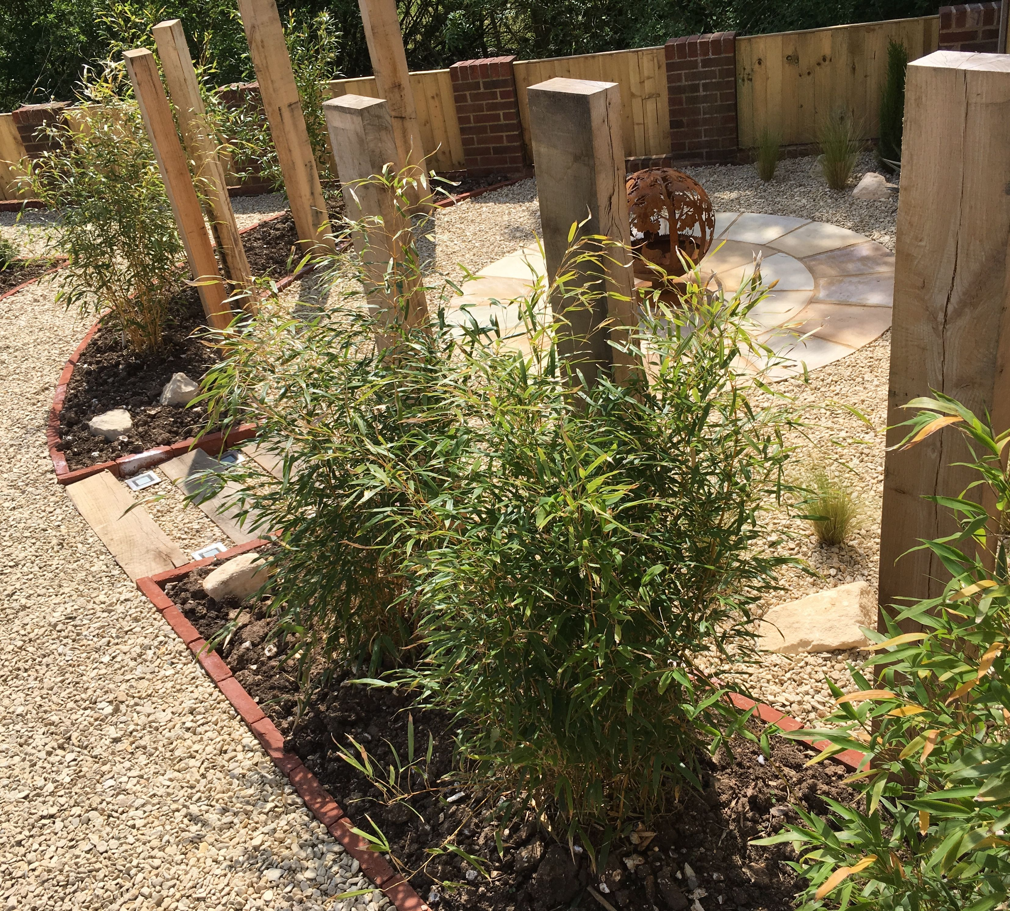 Radial sandstone paving, upright oak sleepers and corten ... on
