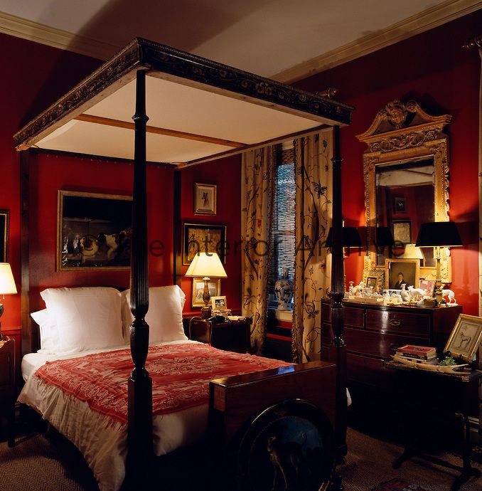 A Four Poster Bed With A Carved Top Dominates This Dark Red Bedroom Which Is