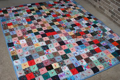 Scrappy, tied quilt. I like the randomness of the color blocks and the red yarn.