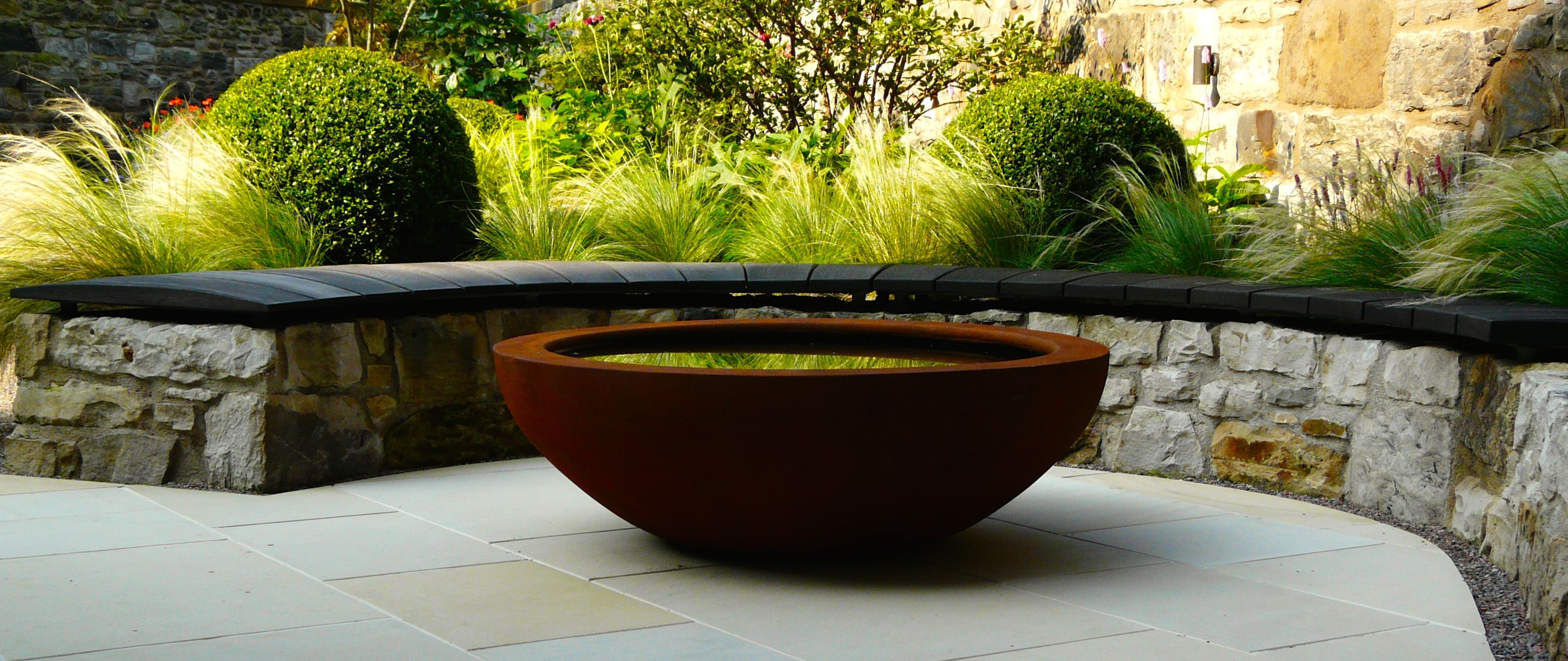 urbis design lily bowl in rust finish with scorched oak bench