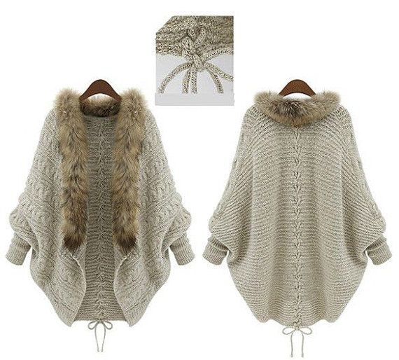Perfect for Fall and the cooler weather this gorgeous faux fur trim cable knit cape sweater pairs with everything. Cable knit sweater has faux fur trim