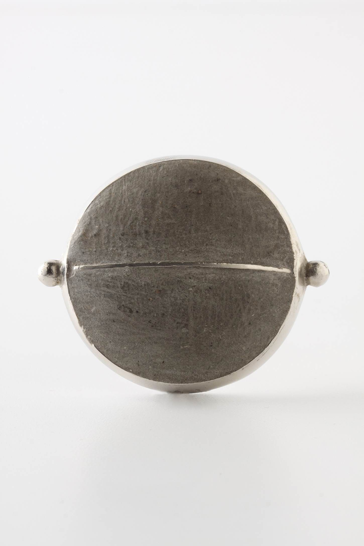 "Door knob A cast-iron frame holds smooth cement slabs, for a sleek, industrial look. Tighten with care   No additional hardware required      Iron, cement, brass      2.25"" diameter      1"" projection      1.75"" bolt can be trimmed to size      Imported"