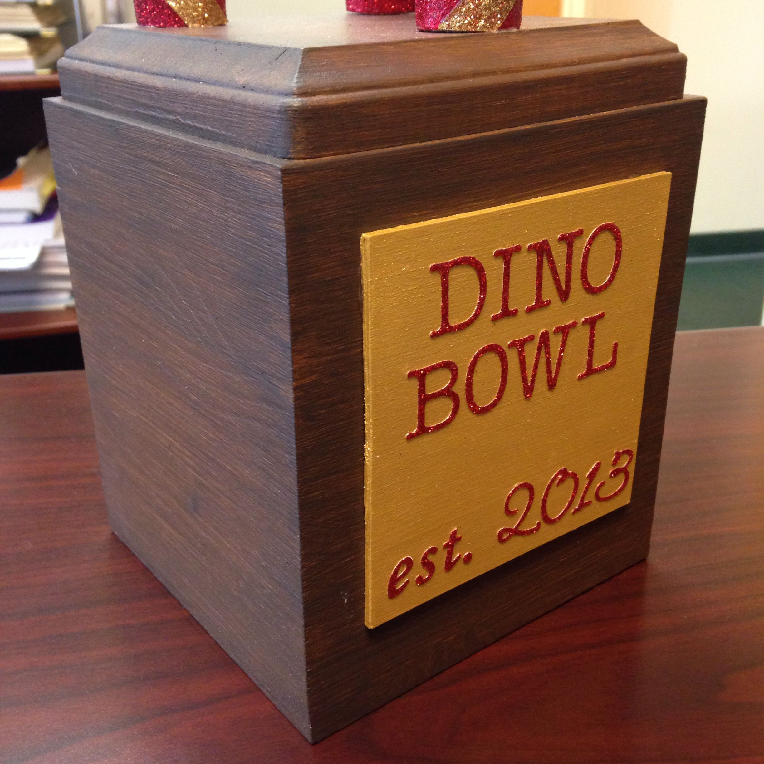 Fantasy football perpetual trophy, close up of base. It's a wooden tissue box cover topped with a wood plaque, then painted with 3 shades of brown Martha Stewart paints. The nameplate is balsa wood painted gold, glued on with E6000. The letters are from the scrapbook department, and sealed with Martha Stewart's decoupage medium. I put some more wooden plaques inside the base to weigh it down. All materials from @Michaels Stores. @Beverly Madden