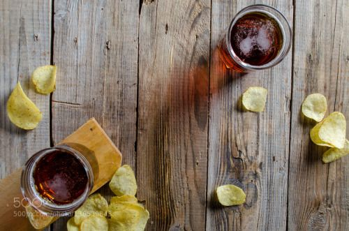 Beer and snacks on rustic wooden textured board from above by amizadon  IFTTT 500px view above alcohol atop beer beverage board chips drink evening foam food glass party