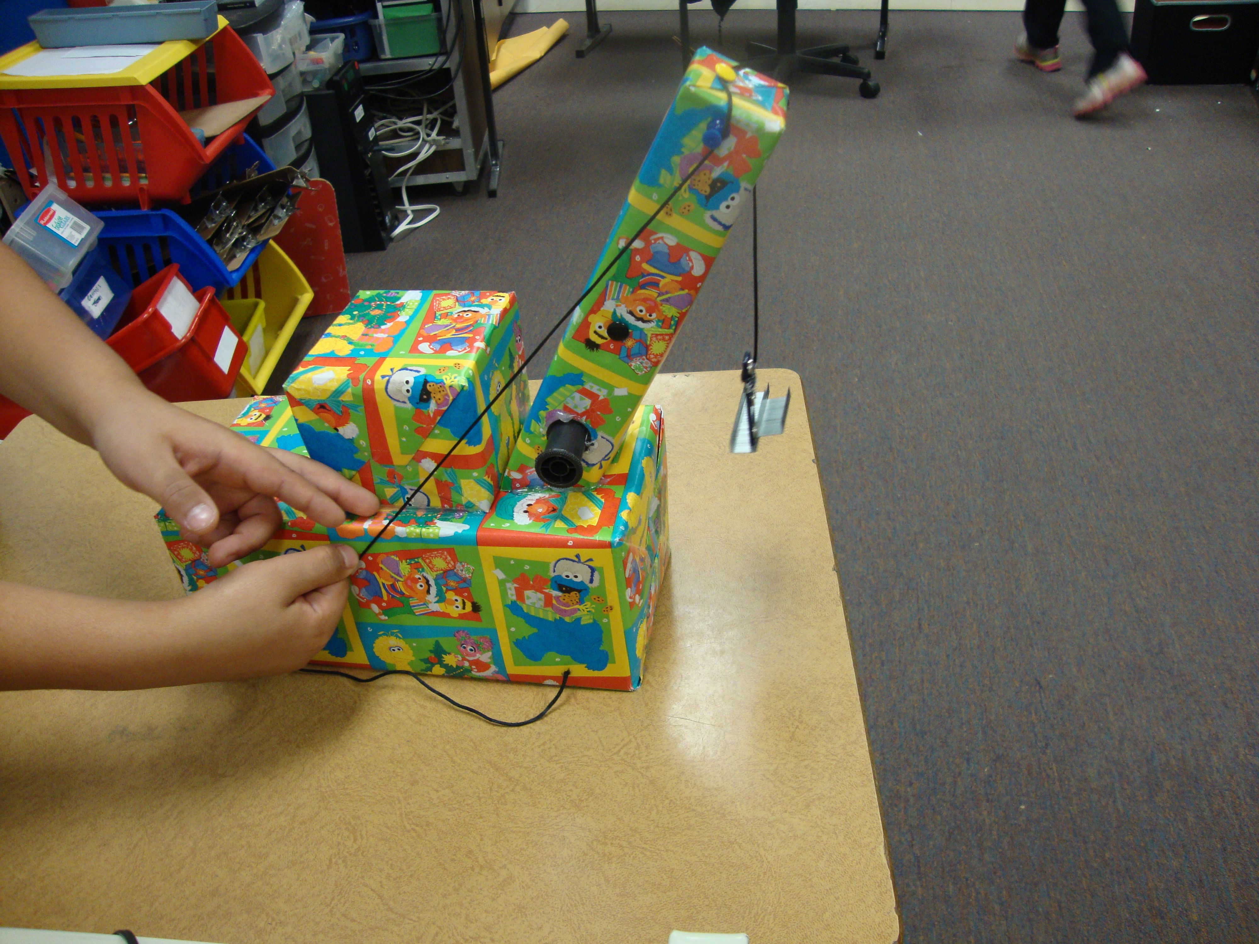 Crane uses a pulley. Student used gift boxes, push pins ...